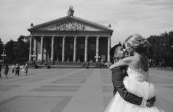 Brudgummen rymmer den vridna bruden i hans armar och Arkivfoton