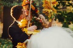 Brudgummen rymmer en brud i en gunga som dekoreras med gul stupad leav Royaltyfri Fotografi