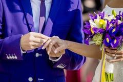 Brudgummen sätter vigselringen på brudens finger Arkivbild