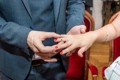 Brudgummen sätter vigselringen på fingret för brud` s arkivbilder