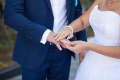 Brudgummen satte cirkeln på brudens hand Fotografering för Bildbyråer