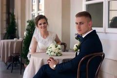 Brudgummen ser kameran, medan sitta på en tabell Fotografering för Bildbyråer