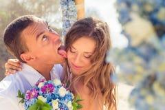 Brudgummen slickar bruden på en bröllopceremoni Arkivbild
