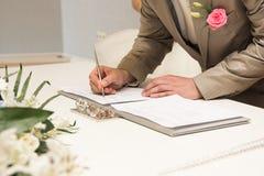 Brudgummen som undertecknar äktenskapslicens eller gifta sig, avtalar Arkivfoton