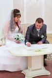 Brudgummen tar ett häfte i papperen arkivfoto