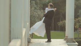 Brudgummen tippar den trevliga bruden som kysser och cirklar henne stock video