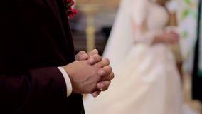 Brudgummen tog händer och bad under ceremonin i kyrkan stock video