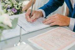 Brudgummen undertecknar förbindelsebesiktningsinstrumenten parförlagor som undertecknar bröllopbarn Royaltyfria Bilder