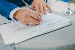 Brudgummen undertecknar förbindelsebesiktningsinstrumenten parförlagor som undertecknar bröllopbarn Arkivfoto