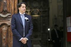 Brudgummen väntar på bruden på den kyrkliga dörren Arkivbilder