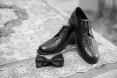 Brudgumpilbåge med skor, svarta skor, brudgumskor, weddingday skor arkivfoton