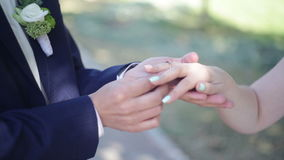 Brudgums hand som sätter en vigselring på brudens finger lager videofilmer