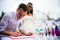 Brudgumteckendokument på registrering av förbindelsen Ett ungt par undertecknar bröllopdokumenten utomhus- bröllop för ceremoni Arkivfoto