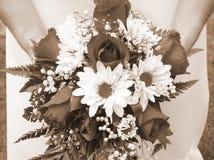 Brudinnehav henne bröllopbukett mot henne horisontalklänning - arkivfoto