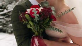 Brudinnehavbukett av blommor som göras av vita och röda rosor Nygifta personer kram, kyss och slaglängd i snöig stock video