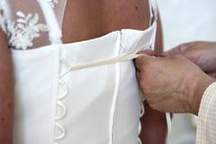 brudklänningen som hjälper henne, satte till bröllop Arkivfoto