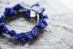 Brudkrona som ligger på en snöra åtservett Brud i den vita klänningen blåa blommor Arkivbild