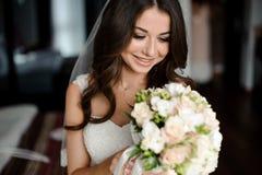Brudmorgonförberedelse Härligt och le bruden i en vit skyla med en bröllopbukett royaltyfri fotografi