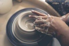 Brudne garncarek ręk pracy z gliną na ceramicznym kole Obrazy Stock