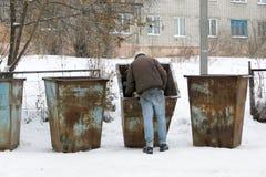 Brudny bezdomny mężczyzna mienia kocowanie dla jajek, stoi kubeł na śmieci Styl życia drałowanie, żyje w ulicach fotografia royalty free