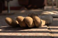 Brudny jeden para rękawiczki lying on the beach na bruku z światłem słonecznym przez one Ochraniający przed brudnymi rękami obraz royalty free