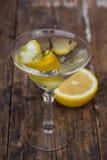 Brudny Martini chłodzący i garnirujący z cytryna skrętem na drewnianym stole obrazy stock