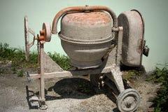 Brudny mini cementowy melanżer w ziemi z little rock, kamienie i wysokie zielone trawy za nim Niedawno używać wyposażenie b obraz stock