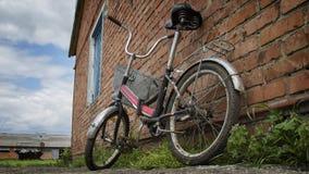 Brudny stary bicykl blisko ściany Zdjęcia Royalty Free