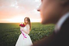 Brudposera och leenden, medan brudgummen väntar på bakgrunden arkivfoton
