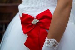 Bruds vita klänning med den röda pilbågen för ton i närbildsikt den blåa detaljblommagarteren snör åt bröllop royaltyfri foto
