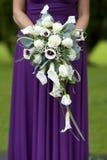 Brudtärna i purple med bröllopbuketten arkivfoton