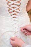 Brudtärna som binder fnuren på bröllopsklänningen royaltyfri bild