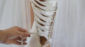 Brudtärna som binder pilbågen på bröllopsklänningen arkivfilmer