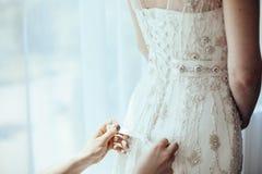 Brudtärna som binder pilbågen på bröllopsklänningen Brud- detalj arkivfoton