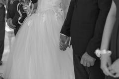 Brudtärnahållhänder under deras bröllopritual arkivbilder