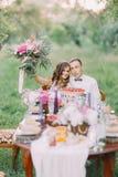 Brudtärnan är hållande övre den älskvärda buketten som kramar med den bästa mannen, och de sitter på brölloptabellen royaltyfri foto
