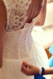 Brudtärnan gör pilbåge-fnuren på baksidan av brudbröllopsklänningen royaltyfria foton