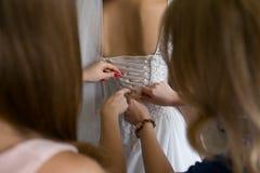 Brudtärnan hjälper bruden att klä arkivbilder