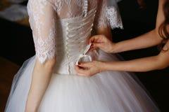 Brudtärnan hjälper bruden att klä royaltyfria bilder