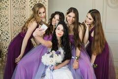 Brudtärnor som hemma tar en selfie på en smartphone och ett skratt under morgonen av bruden Härliga flickor i lilor royaltyfri bild