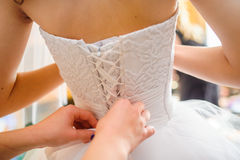 Brudtärnan hjälper bruden att klä Arkivfoto