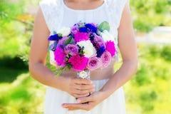Brudtärnan rymmer en bröllopbukett av rosor i purpurfärgade signaler flo Arkivfoto