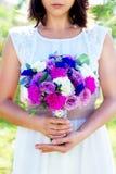 Brudtärnan rymmer en bröllopbukett av rosor i purpurfärgade signaler flo Arkivbild