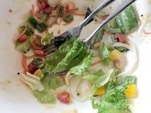 Brudzi naczynie po jeść Caesar sałatki z i łyżki w stronie na stole warzywami i zieleniami w białym ciosie z nierdzewnym rozwidle zdjęcie royalty free