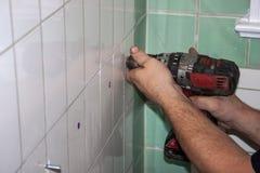 Brudzi ręki hydraulik używa świder tworzyć nowe dziury w zieleni i bielu płytce w staromodnej łazience fotografia stock