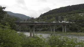 Brug in Bergenrivier Timelapse in de Kaukasische aard van Georgië met bomen en wolken stock videobeelden