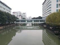 Brug die de rivier kruisen die met dak met hoge gebouwen worden behandeld Stock Foto