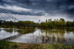 Brug over de rivier met bewolkte hemel Stock Afbeelding