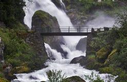 Brug over de stroom dichtbij een krachtige waterval royalty-vrije stock afbeelding