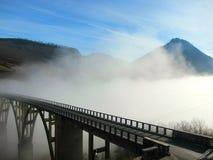 Brug over een bergrivier in de wolk stock afbeelding
